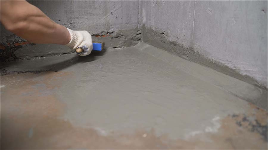 applying waterproofing membrane to corners of bathroom